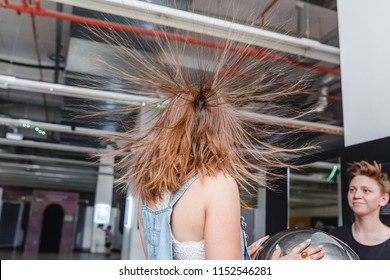 01 JULY 2018, UFA, RUSSIA: Portrait of happy woman with standing hair from static electricity at physics museum