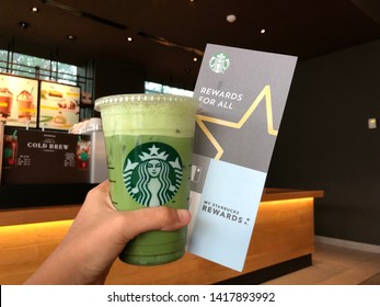 01 June 2019; Bangkok Thailand: Handed Starbucks Cup with Starbucks Rewards Brochure at Starbucks Cafe Coffee Shop