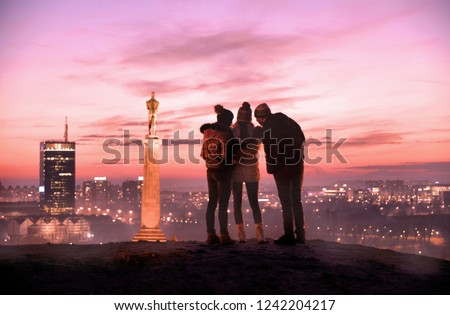 01.01.2017. young people enjoying beautiful sunset on the new part of Belgrade, Danube river and Viktor monument on the hill of the old Kalemegdan fortress. Serbia