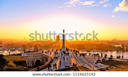 01.01.2018.Sunset light on Danube river, statue and silhouettes of people in fortress Kalemegdan in Belgrade Serbia
