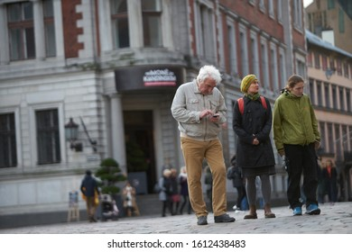 01-08-2019 Riga, Latvia. Gray-haired old men looking phone at old town street.
