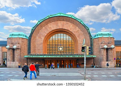 01.09.2016.Helsinki, Finland. People walk on large square in front of Helsinki Central Railway Station in shadows and sun Illuminated classic old buildings in back ground.