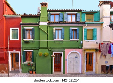 01.12.2018. Burano island picturesque street with small colored houses in row against cloudy blue sky, Venice Italy
