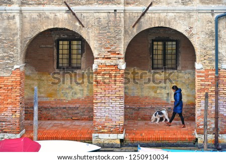 01.12.2018. Venice colorful corners with woman walk with dog under arches of old building and windows.  Venice, Italy