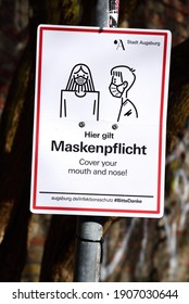 01.21.2021, In Augsburg, a sign is attached to a pole stating that it is mandatory to wear a mask outdoors. This in German and English