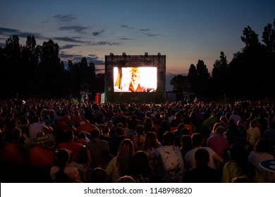 02 August 2018-Bucharest, Romania. People waiting and watching in the public park Herastrau for the movie to start on the projection screen of the open air cinema