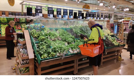 02 December 2018, Istanbul, Turkey: People choosing vegetables in supermarket greengrocer stand.