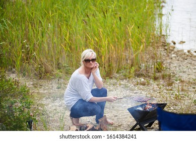 02-08-2017 Riga, Latvia. Handsome female preparing barbecue outdoors for friends