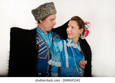 02-27-2010  Moscow.young couple cossacks in country russian clothes look at each other  under one dressed in a lamb cloak. They are  members of dancing group  of cossack culture .