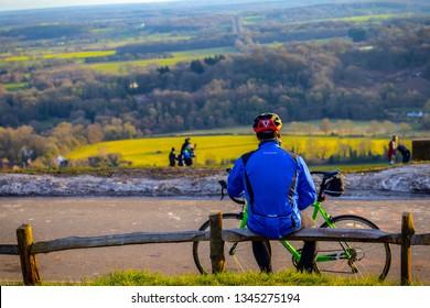 03/02/2019 Surrey, England. Cyclist taking a break and admiring beautiful Surrey Hills