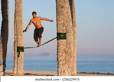 03/02/2019: A young man does a slackline on Ponente beach. Slackline. Equilibrium. Sports on the beach. Physical exercise. Sports. Healthy lifestyle.