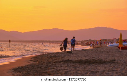 03.08.2018. Romantic scene with young couple  walking on the empty beach at sunset in Maremma, Argentario Grosseto, Tuscany Italy