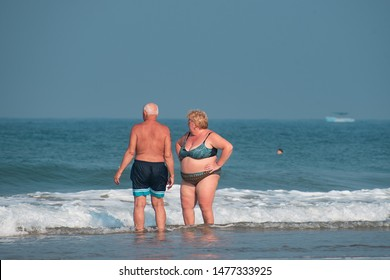 03/10/2019 - Colva, Goa, India: An old white couple standing in shallow sea with blue ocean and sky background. An obese woman in bikini at a beach with a man preparing for a swim in the sea.