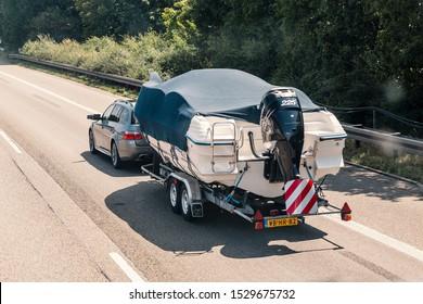 04 August 2019, Nuremberg, Germany: Car transport a big boat at highway road