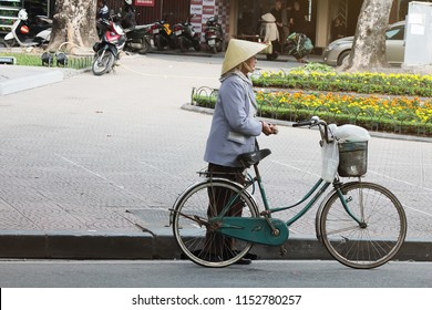 04 January 2016, Hanoi Vietnam :: A Vietnamese old woman with traditional hat and vintage bicycle on the local street in Hanoi