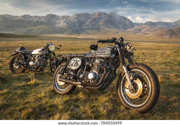 04 September 2016, Campo Imperatore, Abruzzo, Italy: Two vintage custom motorcycle standing in a green field, in the sunset light. Mountains background