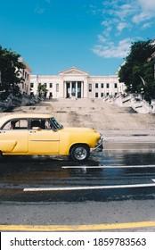 04/01/2013 - Havana, Cuba: A vintage yellow car passing by the University of Havana