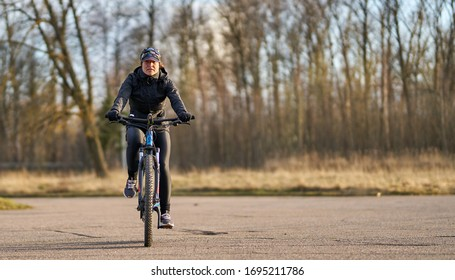 04-04-2020 Riga, Latvia.  A young woman is cycling into the sunset in the park.