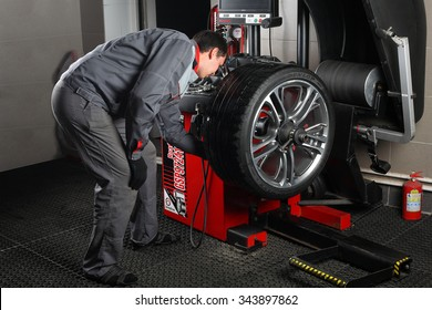 """04.10.2015. Moscow. Car service """"Aquacars"""". Tyre assembling. The worker balances a tire."""