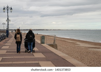04/16/19 Southsea, Portsmouth, Hampshire, UK two woman walking along a beach in winter one woman pushing a double pushchair