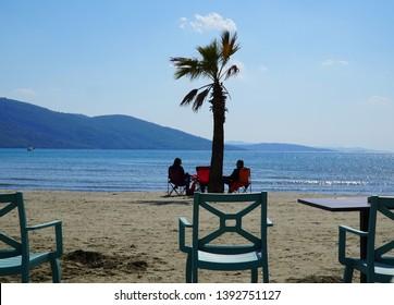 04/20/2019- Akyaka, Mugla, Turkey. Couple sitting on the chair on the beach watching the view.