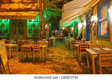 04/23/2019- Balikesir, Turkey. Cunda Island, also called Alibey Island  is the largest of the Ayvalık Islands archipelago in Turkey. View of the street with restaurants at night.