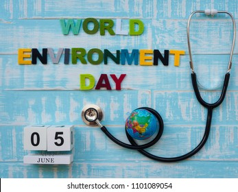 05 JUNE wooden block calendar globe and stethoscope with WORLD ENVIRONMENT DAY text on blue wooden background.