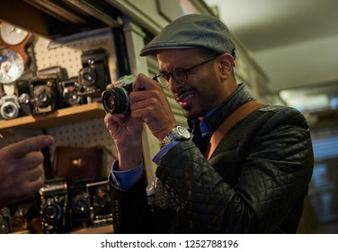 05/05/2017 london, england, A young arabic male tourist in london on the world famous carnaby street, looking and trying out retro film and movie cameras in an antique camera shop.