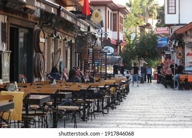 05.11.2019 - Antalya, Turkey. Cafe of the narrow street of the resort town of Turkey. People sitting at tables at outside restaurant. Ancient district with beautiful architecture.