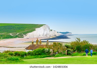 05.22.2018 Cuckmere Haven, Sussex, UK. coastguard cottages at seaford head with a view of the seven sisters cliffs in the background