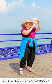 05.22.2018 Eastbourne, Sussex, UK. Middle aged woman taking a selfie on eastbourne pier