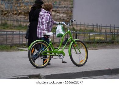 06-03-2020 Riga, Latvia Image of a young woman walking with her bicycle