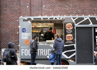 06-03-2020 Riga, Latvia street sale and people concept - happy young saleswoman at food truck serving male customer.
