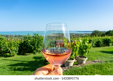 06.08.2019. - Csopak, Hungary: Drining rose wine over Lake Balaton in Csopak Hungary at St. Donat winery with nice view