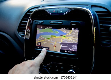 06/14/2019 Portsmouth, Hampshire, UK A close up of a finger operating a sat nav or satellite navigation unit inside a car