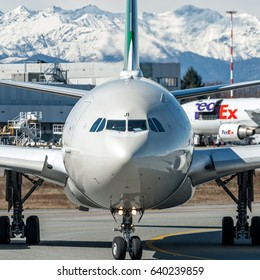 07 March 2017 Airbus A330 Alitalia taxiing for departure from runway 35R Milano Malpensa, Italy. The most important Italian Airline and it was purchased for 49% by Ethiad. Alps mountain in background