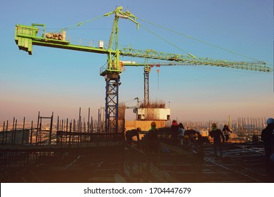 07-01-2020, Bangkok, Thailand. Workers are constructing high-rise building by pouring concrete on steel that has already been prepared on the rooftop with crane for move material at the sunset time