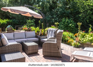 07.07.2017 Kent, UK. Modern rattan patio furniture with dining table and chairs with parasol in the background all surrounded by greenery and flowers