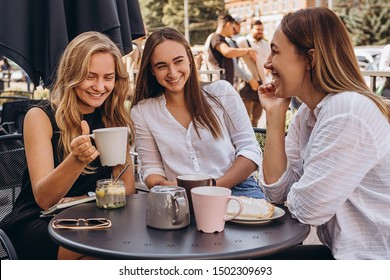 07.09.2019 Vinnitsa, Ukraine: company of best friends, pretty girls brunettes and blondes on the summer cafe terrace, drinking refreshing summer drinks, chatting, joking, having fun, smiling.