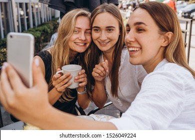 07.09.2019 Vinnitsa, Ukraine: company of best friends, pretty girls brunettes and blondes on the summer cafe terrace, drinking coffee, chatting, joking, having fun, smiling, photographed on the phone