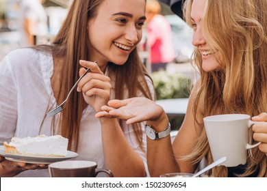 07.09.2019 Vinnitsa, Ukraine:  two best friends meet in a cafe, two pretty girls jokes and have fun, drinking tea, eating cakes at a table outside, selective focus