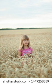 07.11.2019, Teplik, Ukraine. A wheat field outside the city A little girl is grieving against the background of the wheat field and the cloudy sky. Emotions of a small child.