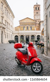07.2018 - Trastevere district, Rome, Italy - Iconic Vespa brand scooter of red color at a piazza di Santa Maria. Basilica di Santa Maria in Trastevere is in background.