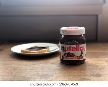 08.04.2019 Parma, Italy: Nutella jar on the wooden table and a white plate with a tost on it with chocolate butter