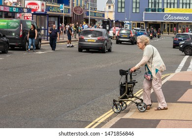08/04/2019 Portsmouth, Hampshire, UK An elderly lady crossing the road using a mobility aid or a Zimmer frame