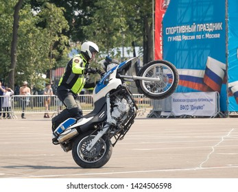 08/06/2019 Russia, Moscow. The police officer on the motorcycle shows professional driving of the stuntman. The officer goes on one back wheel, the motorcycle costs vertically