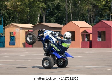 08/06/2019 Russia, Moscow. The police officer on the ATV shows professional driving of the stuntman. The officer goes on the ATV, the car costs vertically on two wheels