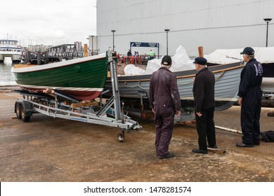 08/13/2019 Portsmouth, Hampshire, UK Three elderly men standing next to newly restored wooden boats on a slipway