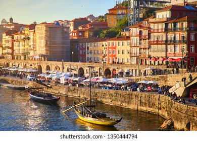09 of December, 2018 - Porto, Portugal: Old town ribeira aerial promenade view with colorful houses, Douro river and boats. Concept of world travel, sightseeing and tourism