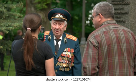 09.05.2018 - Kyiv, Ukraine. Woman taking a picture of elderly colonel veteran outdoor. Defender of Motherland. Anniversary of Victory in Great Patriotic War.